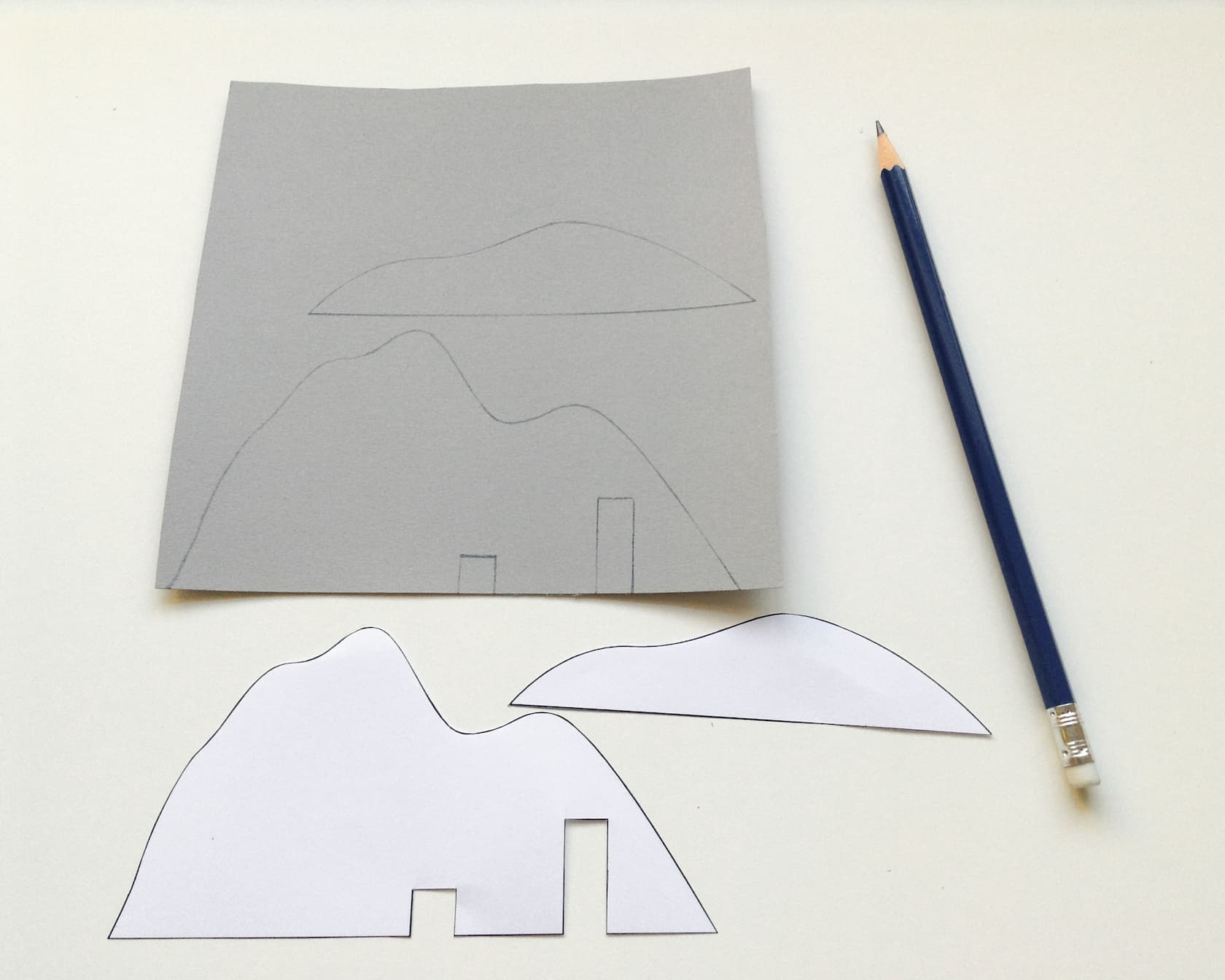 Draw the mountain shapes onto some grey card