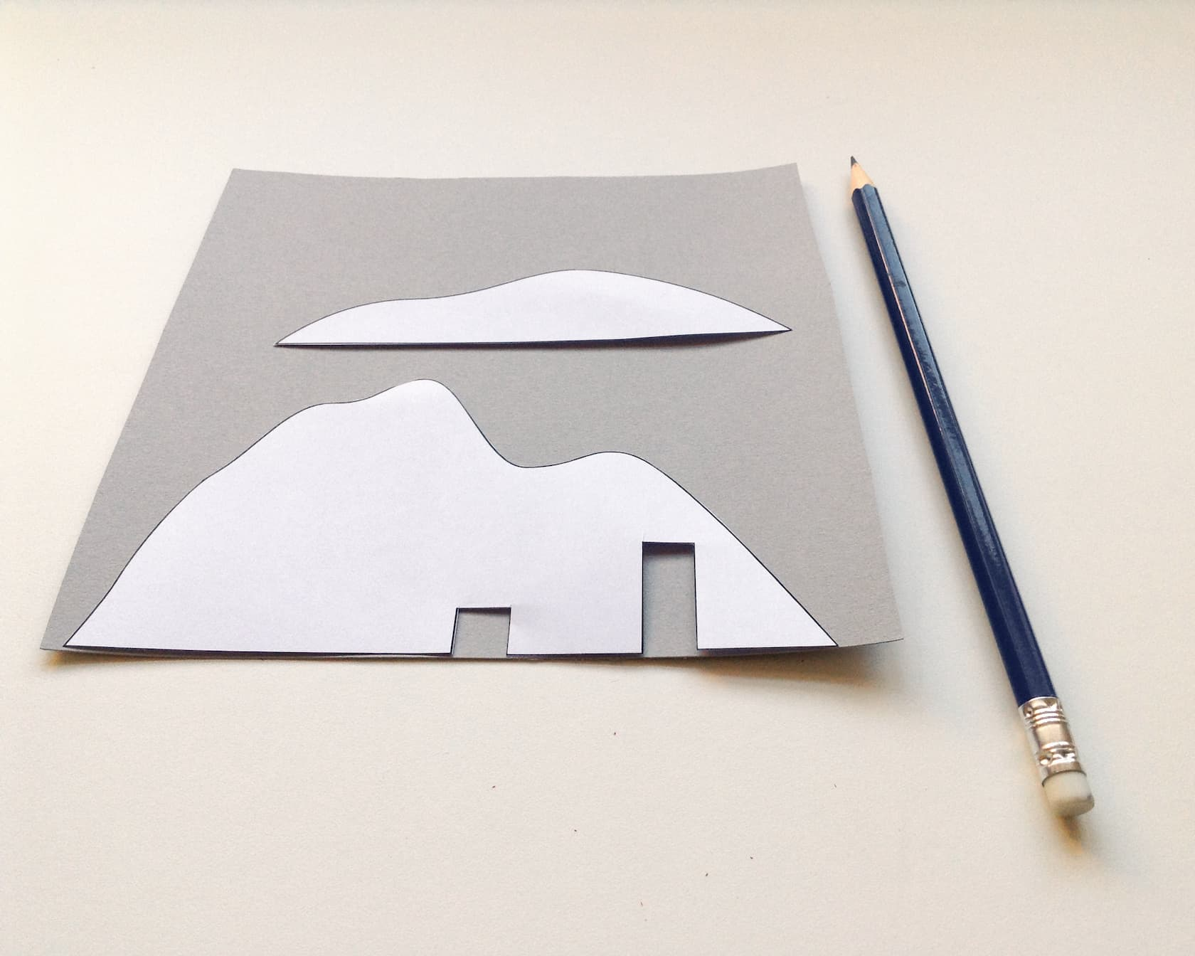 Use the mountain shapes as a stencil onto the grey card