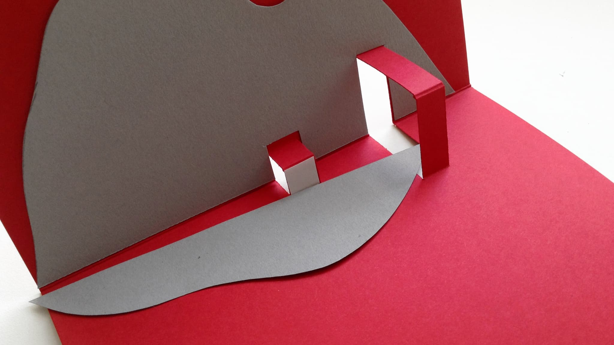 Stick the smaller mountain shape onto the smaller pop-out support