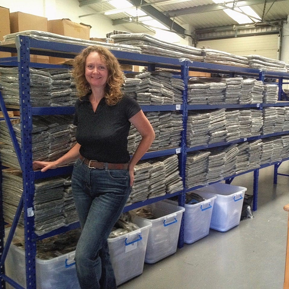 Sally Phillips of Chimney Sheep Ltd., standing next to racks of Herdwick fleece