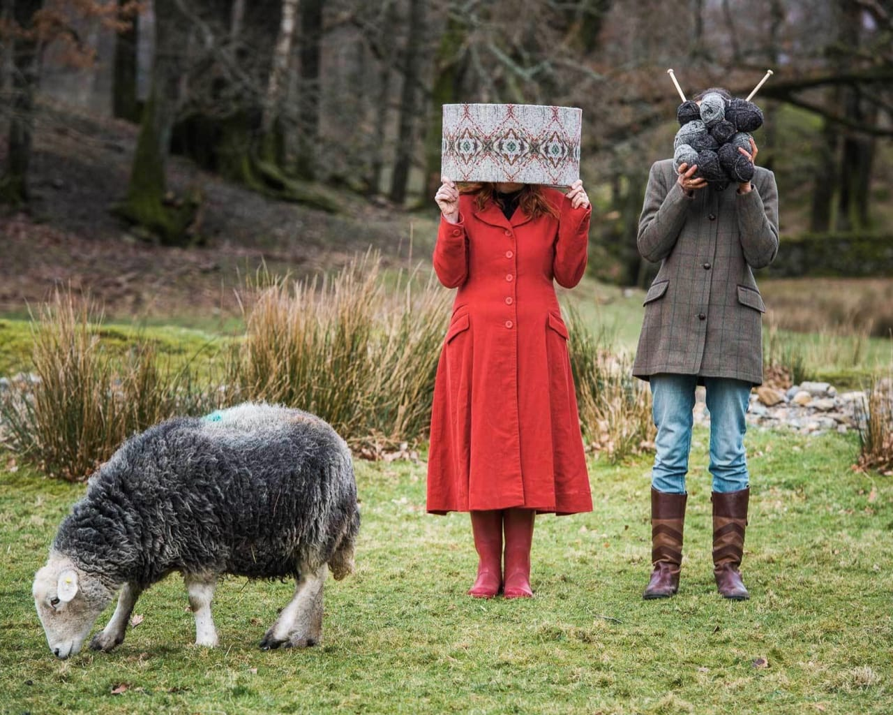 Rachel and Alice of Cable & Blake pose with their products next to a grazing Herdwick sheep