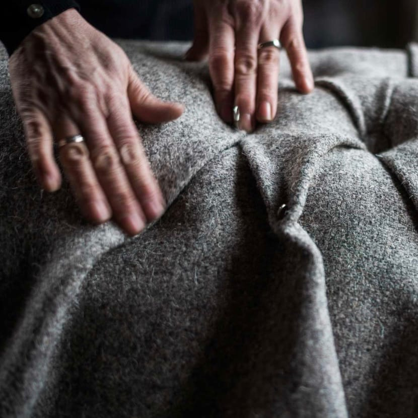 Hands apply the finishing touches to a Herdwick fleece decorated upholstery