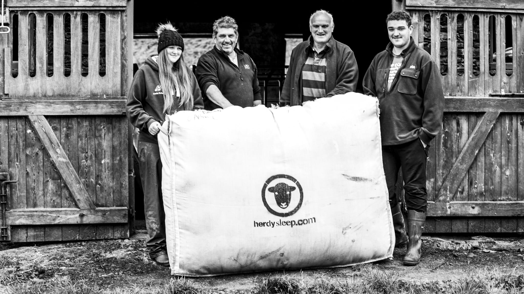 Shepherds and farmers, young and old, hold up a woolsack of Herdysleep fleece