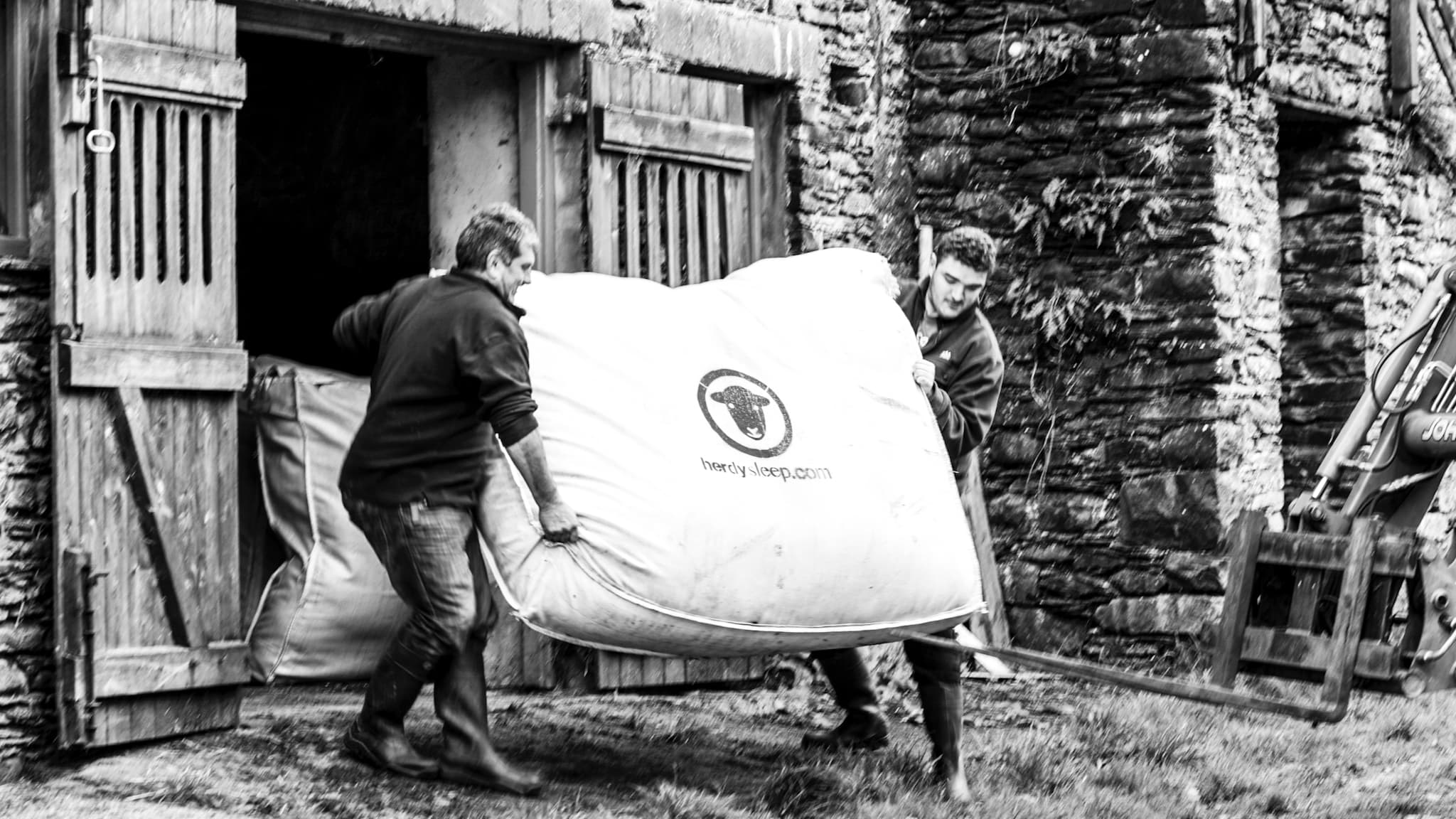 Two Lake District fell farmers carry a heavy woolsack filled with Herdwick wool into a barn, ready for collection by Herdysleep. Photo ©Spencer Hannah.
