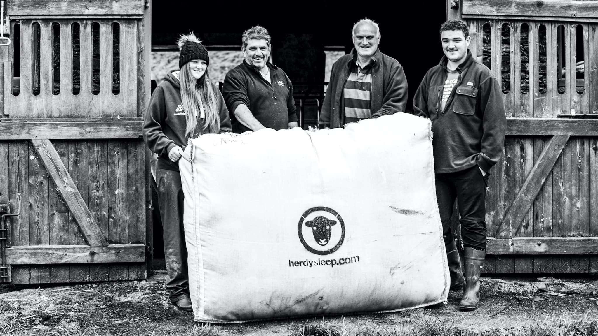 Lake District farmers smile for the camera with a woolsack filled with Herdwick wool. Photo ©Spencer Hannah.