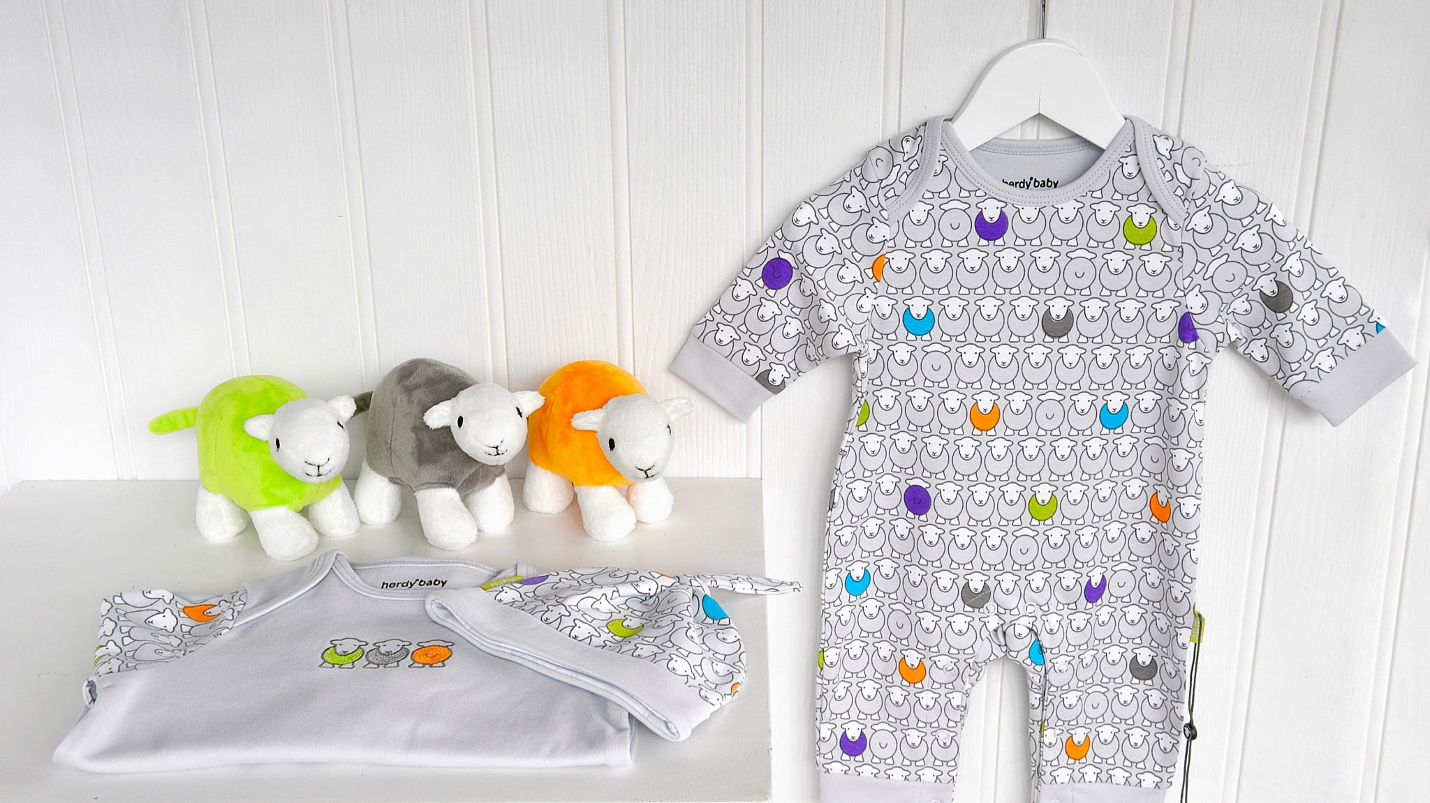 Our Herdy Baby Grow with a Herdy Baby Hat and Embroidered Baby Grow and three Baby Herdys