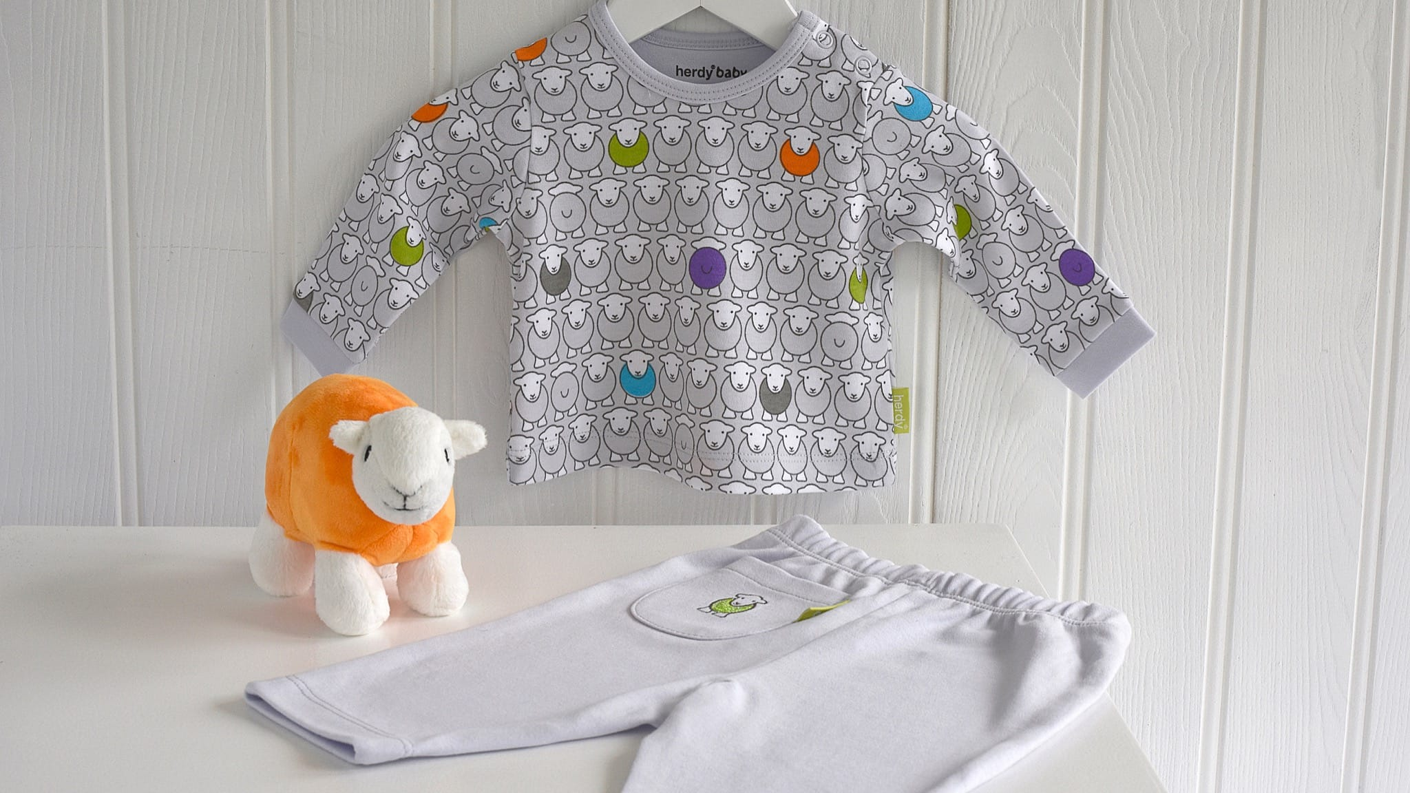 A Herdy Baby Top & Pants set, with an orange Baby Herdy in between