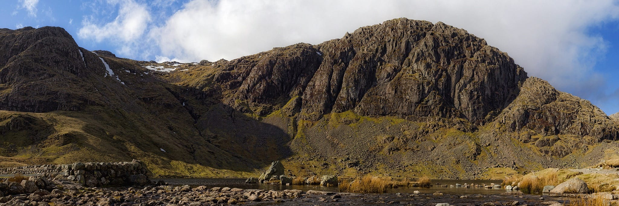 A view of the cliffs of Pavey Ark and Harrison Stickle from the shore of Stickle Tarn. Photo by nagualdesign (CC BY-SA 4.0)