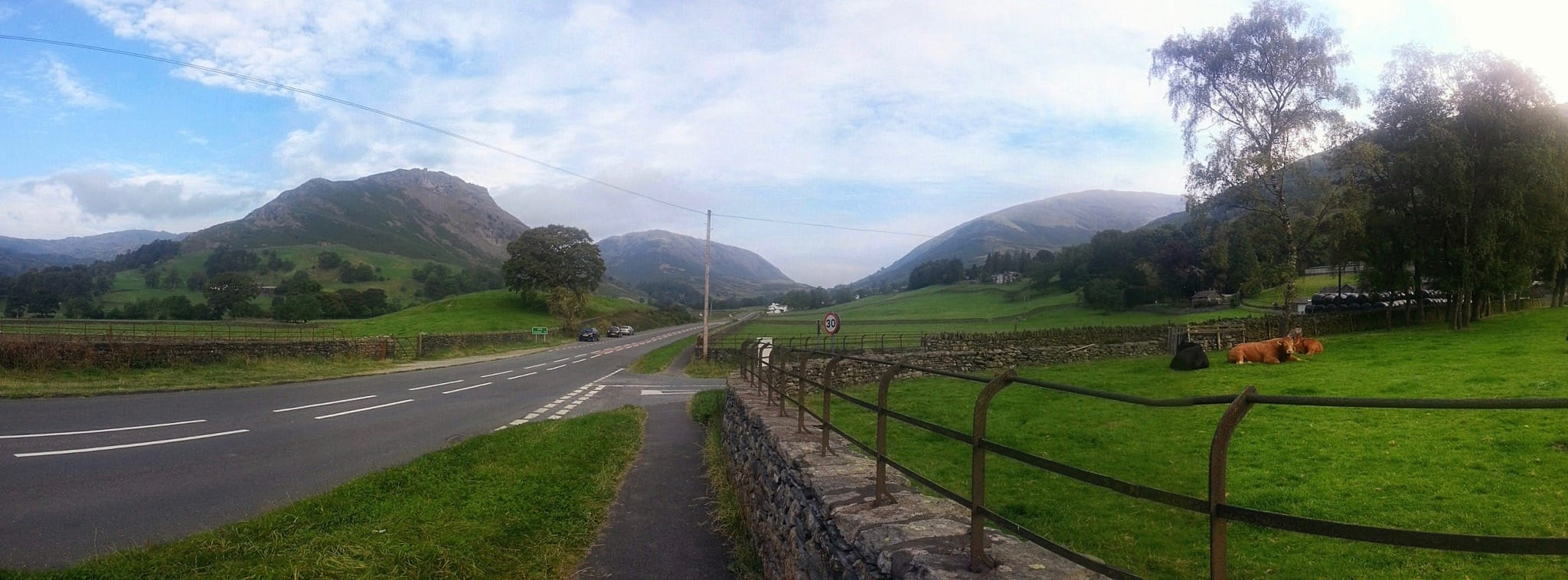 A panoramic view north of Grasmere village from near the A591 trunk road. Helm crag on the left, Steel Fell in the centre, Seat Sandal on the right