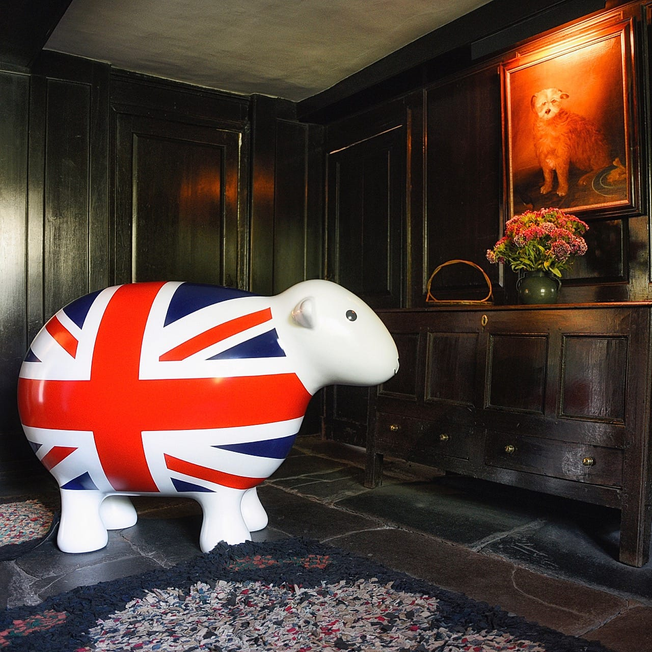 Giant GB Herdy inside Dove Cottage and its wooden clad walls and antique furniture, looking at a portrait painting of a dog