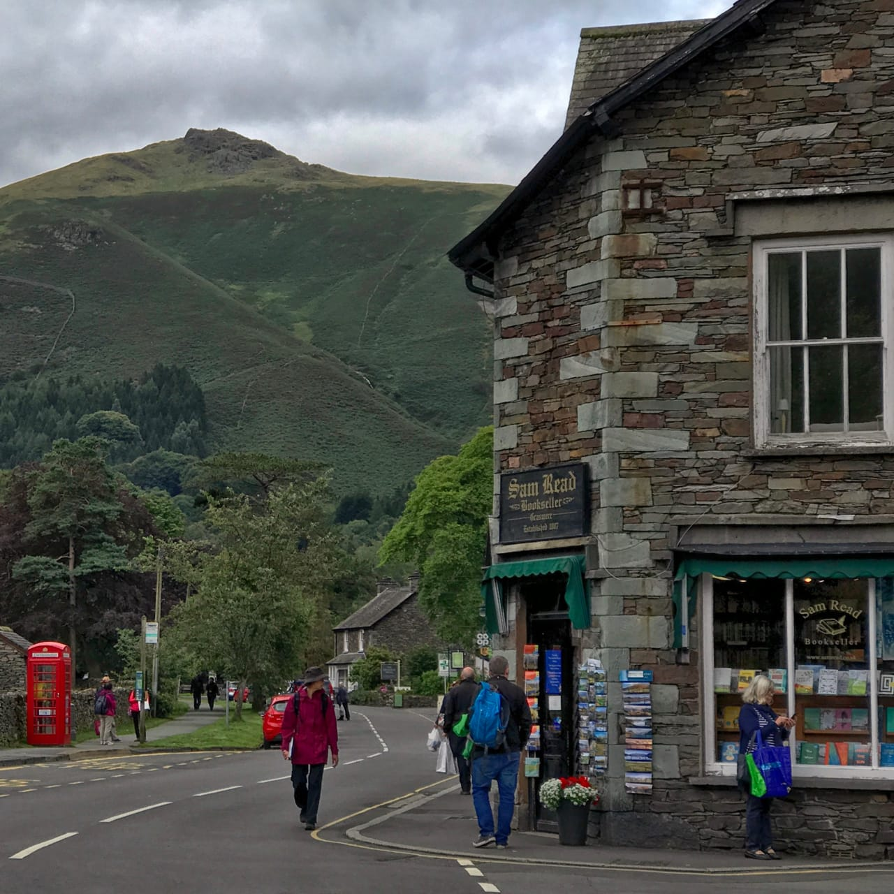 The front of Sam Read Bookshop with the looming summit of Heron Pike in the distance