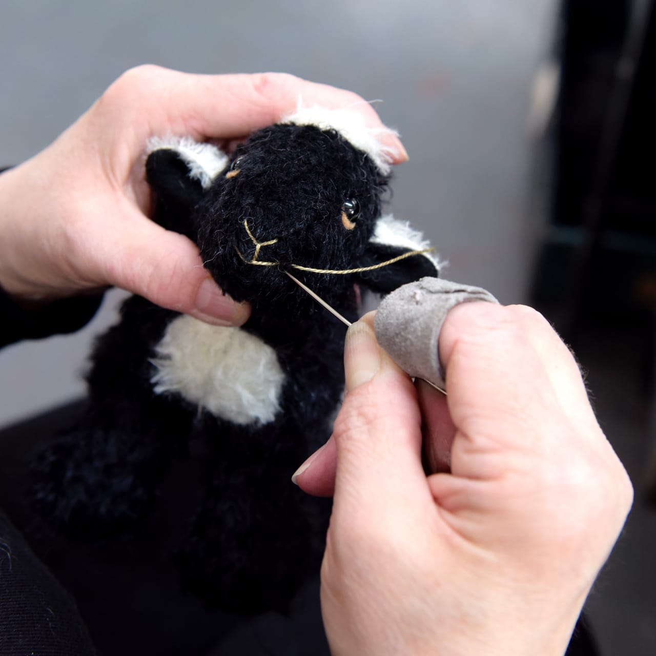 Merrythought worker putting the final touches together on the face of My Herdy Lamb