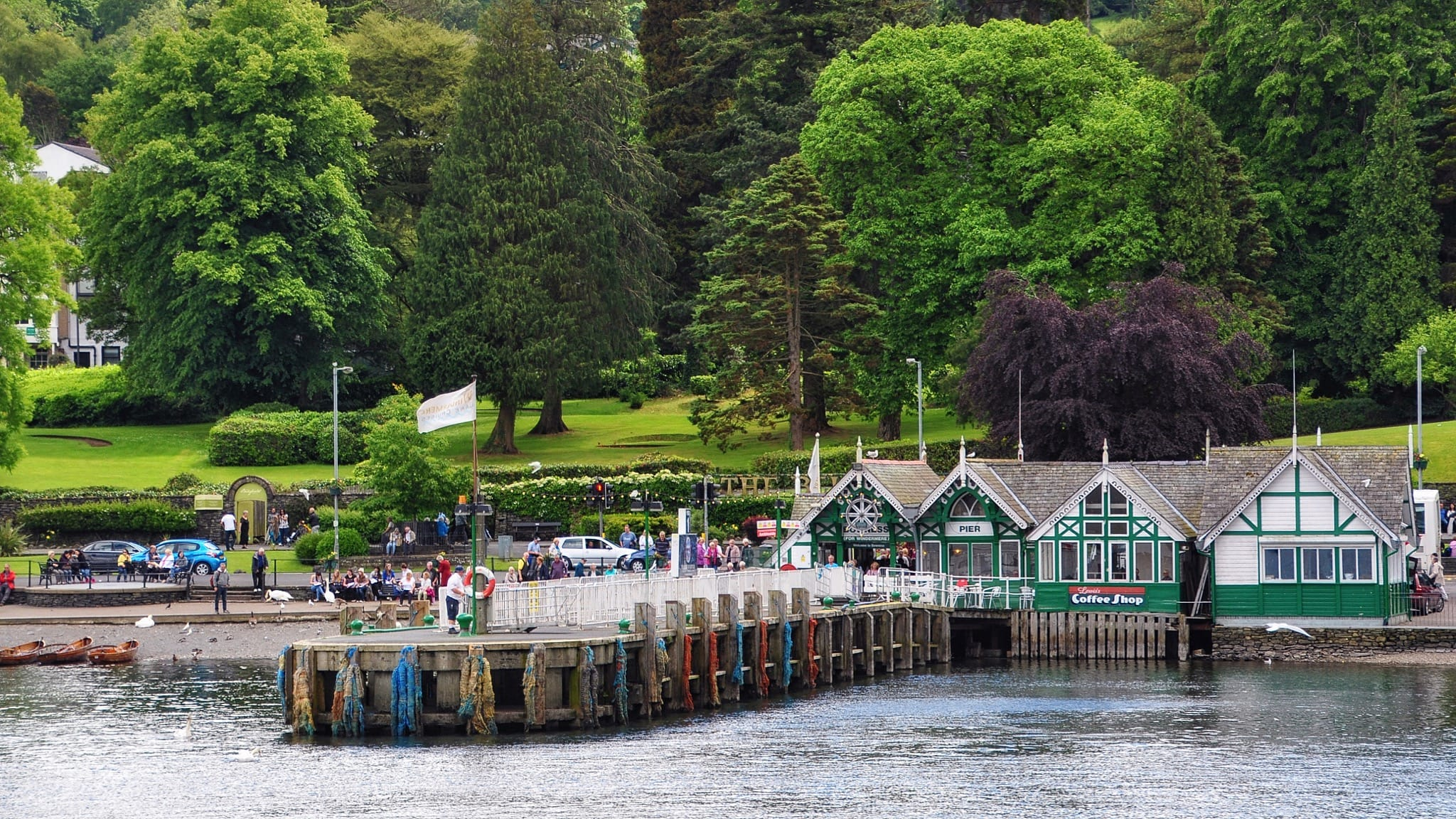A view of Bowness Pier from the lake of Windermere, with green leafy trees behind it. Photo by Nilfanion, licensed CC-BY-SA-4.0.