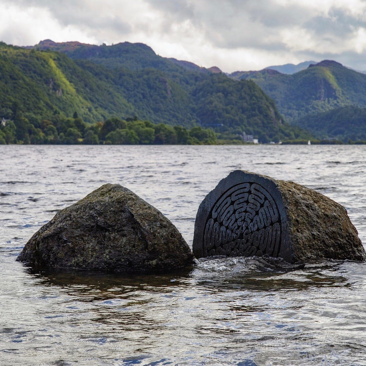 The Hundred Year Stone, half submerged in the waters of Derwentwater, with the Borrowdale fells in the distance.