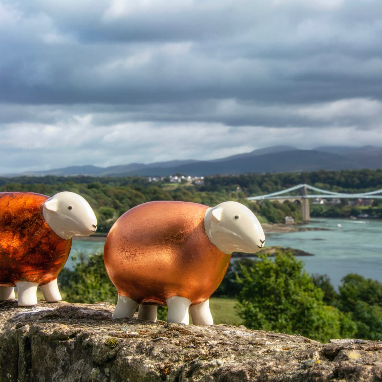 The two Copper Herdys perch above the Menai Strait with the Menai Bridge and the Snowdonia mountains in the distance.